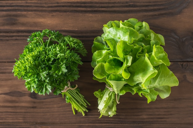 パセリとレタスの葉はテーブルの上に束ねられています。健康的な食事の概念。フラットレイ。