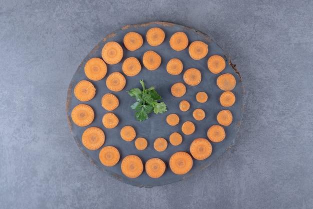 Доска петрушки и моркови нарезанная, на мраморной поверхности.