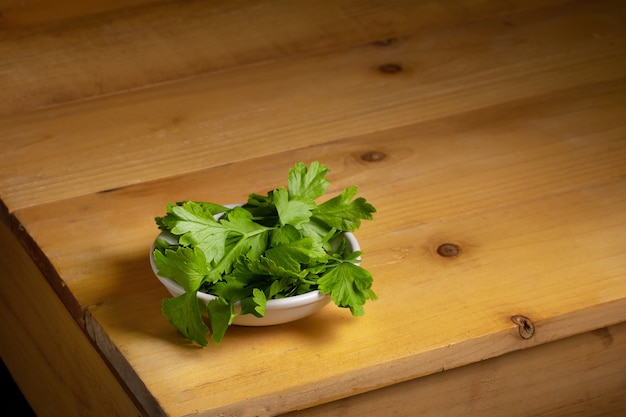 Parsley in a bowl over a wooden table