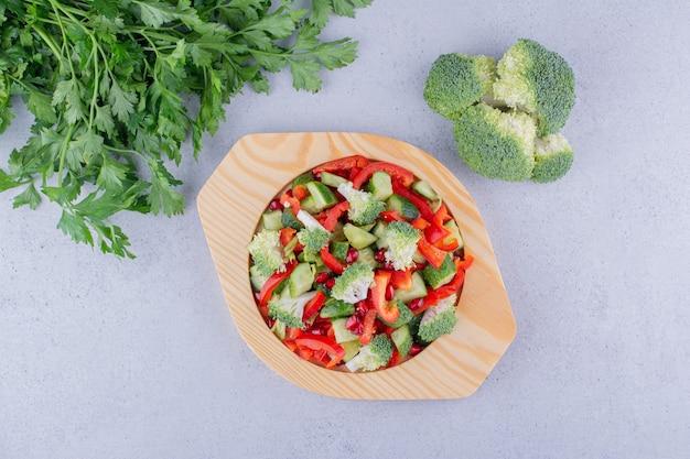 Пучок петрушки, горсть брокколи и блюдо салата на мраморном фоне. фото высокого качества