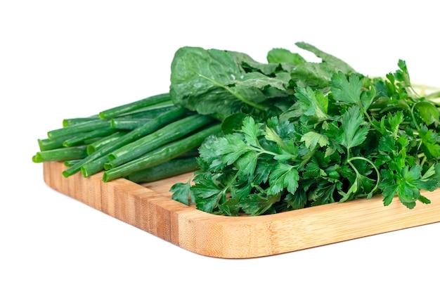 パセリ、ネギ、木の板の生きているクレスが分離されました。野菜。