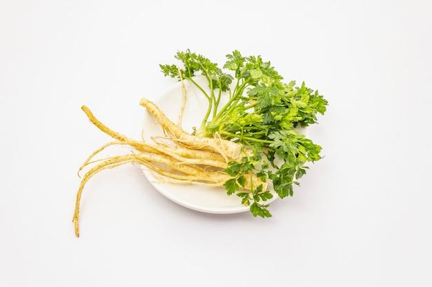 Зелень петрушки и корни на белом фоне