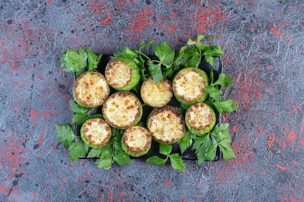 Foglie di prezzemolo che adornano un piatto di zucchine fritte su uno sfondo di colore scuro. foto di alta qualità