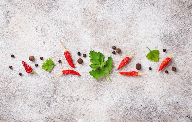 Parsley, red chili and black pepper on light background