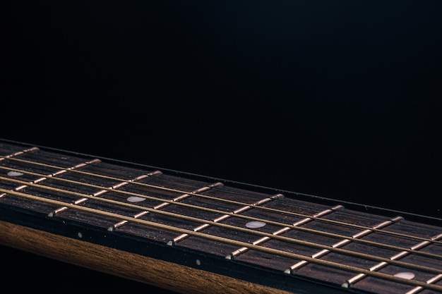 Part of an acoustic guitar, guitar fretboard on a black background.