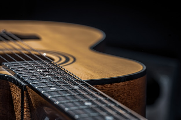 Part of an acoustic guitar, guitar fretboard with strings on a black background with highlights.