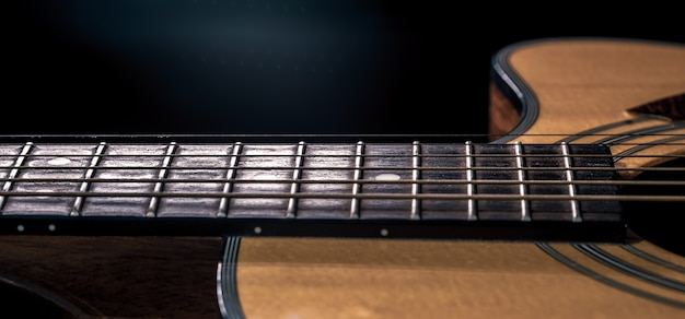 Part of an acoustic guitar, guitar fretboard with strings on a black background.