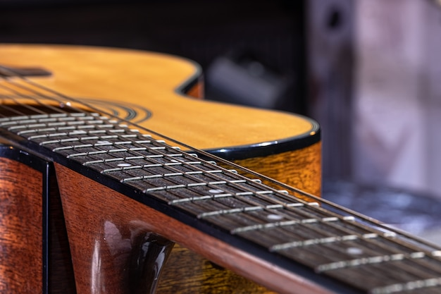 Part of an acoustic guitar, guitar fretboard with strings on a blurred background.