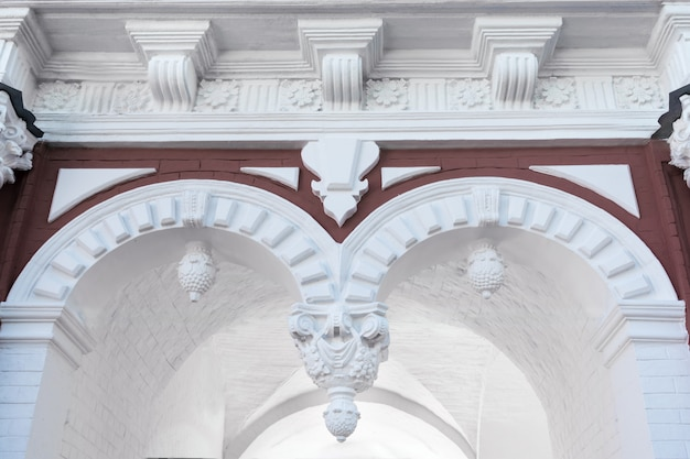 Part of an architectural building with arches, stucco, pilasters.