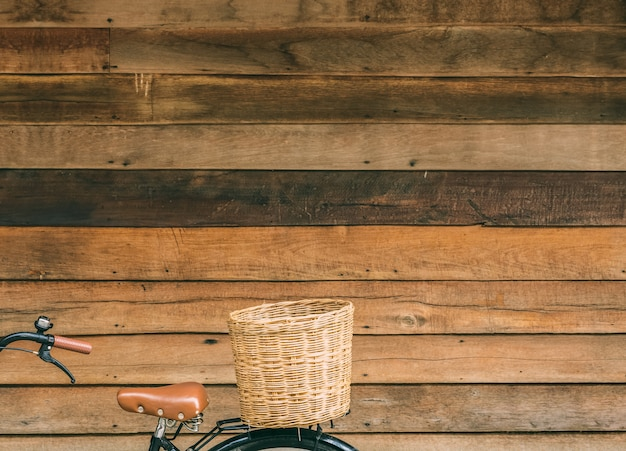 Part of bicycle with basket on wooden house wall