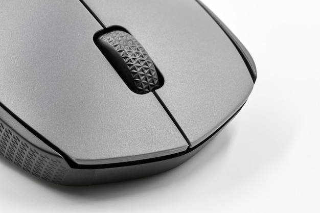 A part of black optical wireless computer mouse on white background. closeup