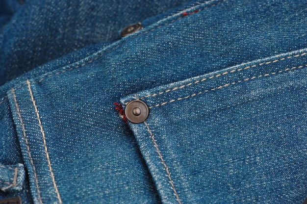 Part of the blue denim pants with pockets and rivets, close-up