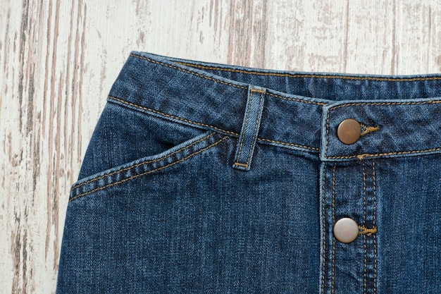 Part of the blue denim skirt. wooden background, fashionable concept
