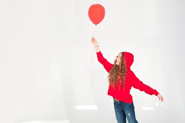白灰色の背景で楽しんでいる赤い気球を手に持っている素敵な魅力的で面白い陽気な10代の子供の女の子の部分ボディサイズのビュー。