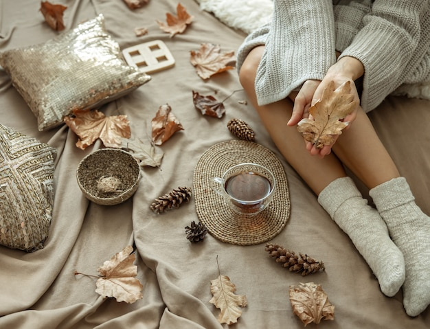 Part of the body, a woman in a cozy bed with a cup of tea among the autumn leaves.