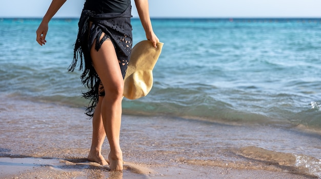 Part of the body of a woman walking along the seashore on a hot summer day.