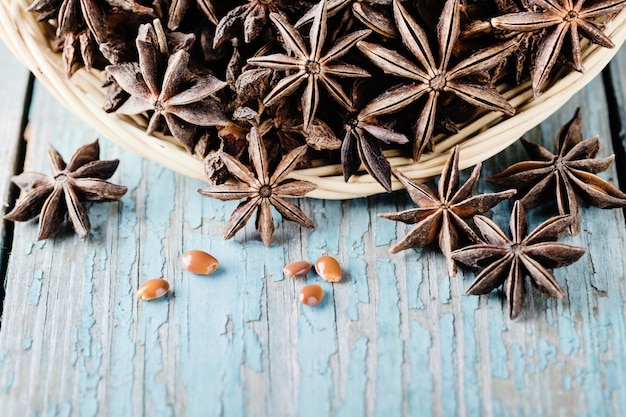 Part of bowl with star anise on blue wood