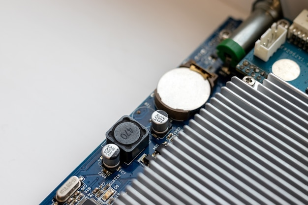 Part of computer motherboard with capacitors battery and cooling radiator