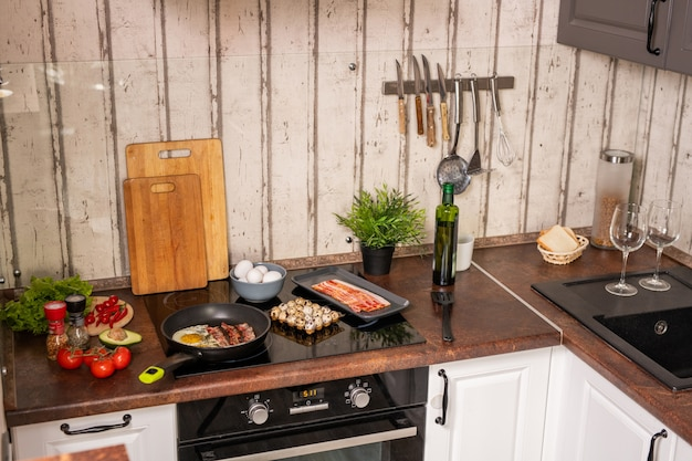 Part of contemporary kitchen with sink and electric stove with frying bacon and eggs surrounded by kitchenware and food products