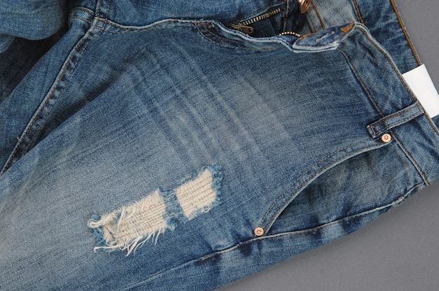 Part of damaged denim pants with pocket and unbuttoned zipper, close-up