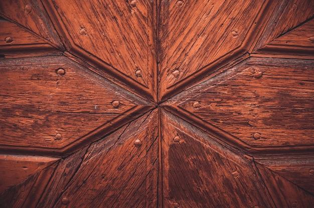 Part decorative old wooden door with textured pattern.