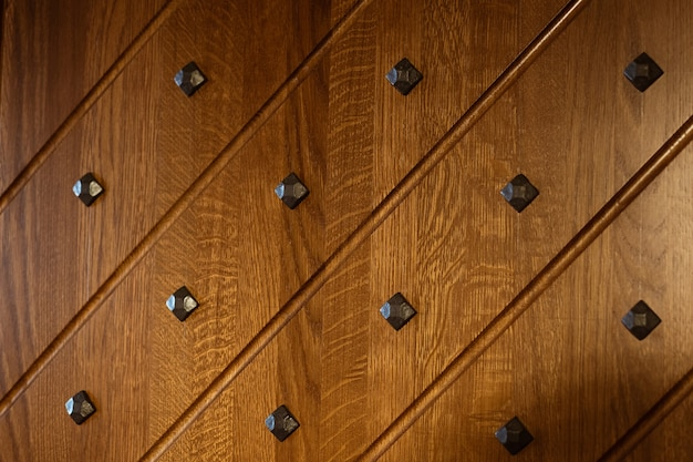 Part of the decorative wooden surface decorated with black metal rivets and diagonal lines shot by