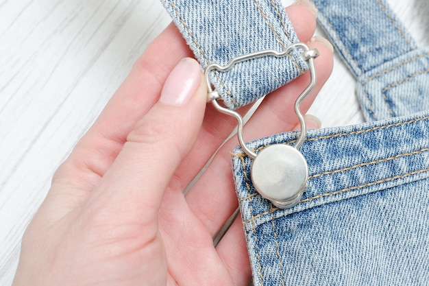 Part of denim overalls in a female hand. fashionable concept
