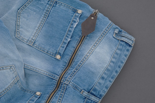 Part of denim pants with back pocket and zipper, close-up