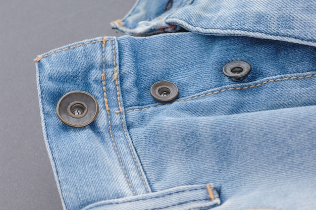 Part of denim pants with pocket and unbuttoned buttons, close-up