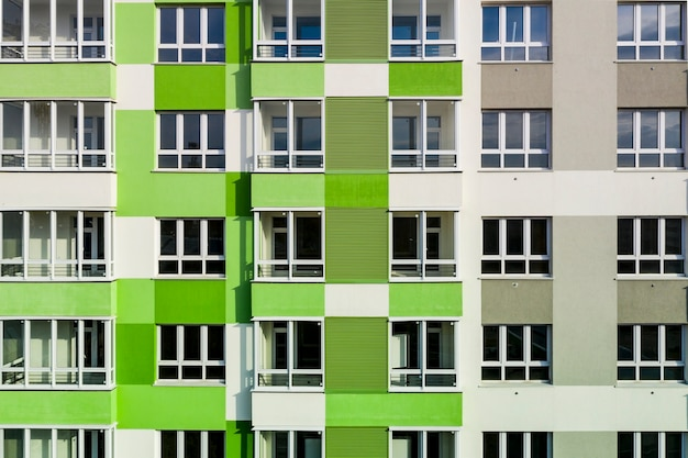 Part of the facade with windows of a new house with green-gray walls