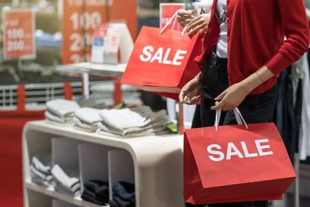 Part of female mannequin dressed in casual clothes holding the sales paper shopping bag