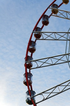 Part of ferris wheel with cabins on the background of cirrus clouds and blue sky