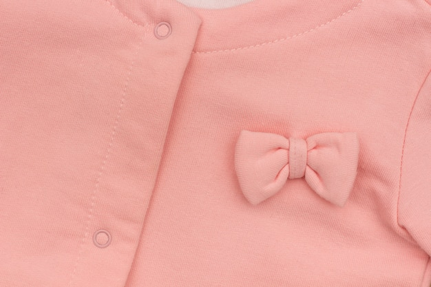 Part girl's pink elegant jacket with bow close-up, background texture