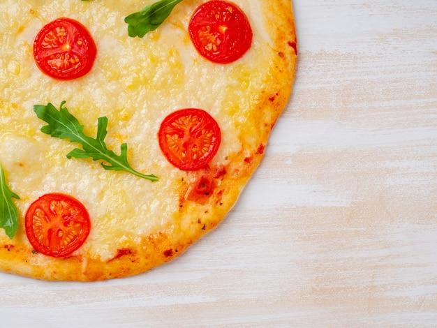 Part of hot homemade italian pizza margherita with mozzarella