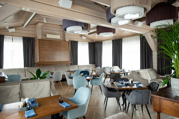 Part of luxurious interior of modern restaurant with served tables and soft velvet armchairs around them