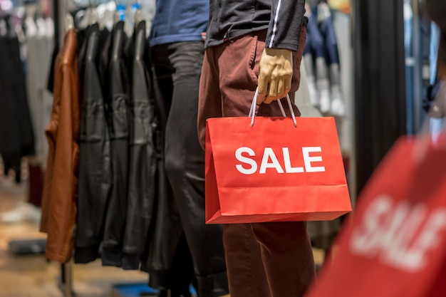 Part of male mannequin dressed in casual clothes holding the sales paper shopping bag