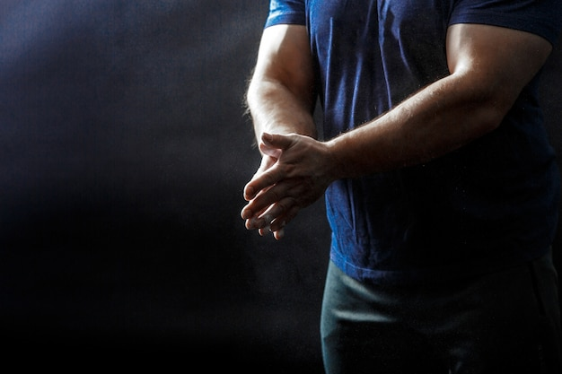 Part of male's corpus, in black t-shirt with hands squeezed together