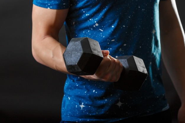 A part of man's torso, wear blue t-shirt with gymnastic dumbbell in right hand