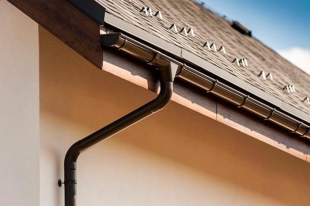 Часть коричневой крыши с трубой ливневой канализации у дома