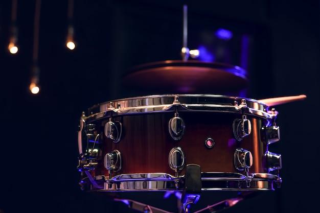 아름다운 조명으로 어둠 속에서 드럼 키트의 일부입니다. 콘서트 및 성능 개념.