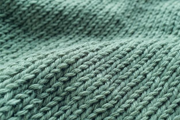 ニットプロジェクトの一部、セーターのクローズアップ、トップビュー。古典的なループは、イタリアのウール糸の緑の糸で作られています。テクスチャ背景。