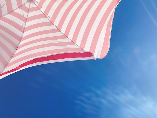 Часть полосатого пляжного зонтика против красивого голубого неба, вид снизу. туризм и летняя концепция, слэс для текста.