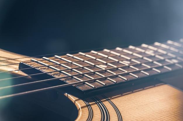 어쿠스틱 기타의 일부, 하이라이트가 있는 검정색 배경에 현이 있는 기타 지판.