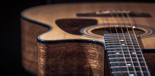 어쿠스틱 기타의 일부, 검정색 배경에 현이 있는 기타 지판.