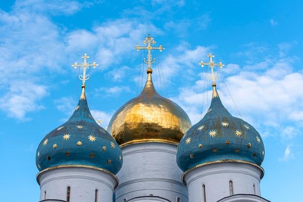 Часть древней православной русской церкви с золотым крестом и куполом в троице-сергиевой лавре в сергиевом посаде
