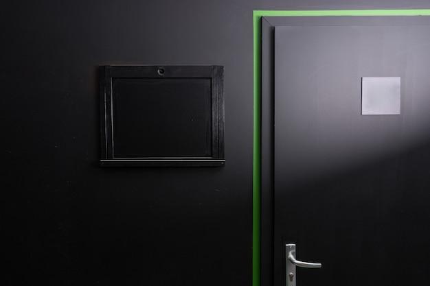 緑のエッジの輪郭と銀のドアハンドル、黒い壁に黒い覆われた窓のハッチが付いた黒いドアの一部