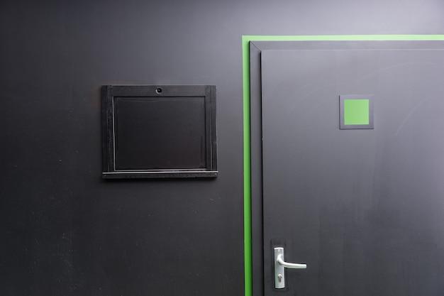 銀色のドアハンドル、緑色ののぞき見正方形と輪郭、黒い壁に黒い覆われた窓のハッチが付いた黒いドアの一部