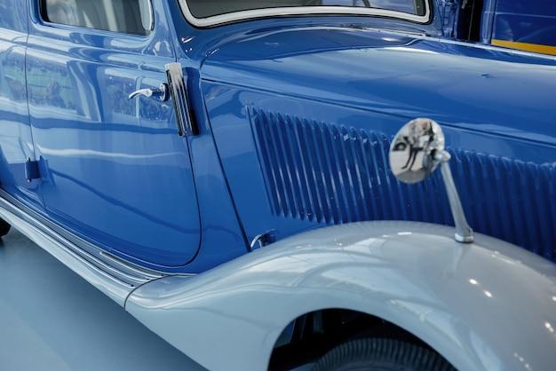 Часть синего совершенного полированного старинного автомобиля, стоящего в помещении на белой плитке.