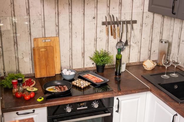 台所用品と食品に囲まれた揚げベーコンと卵を備えたシンクと電気ストーブを備えた現代的なキッチンの一部