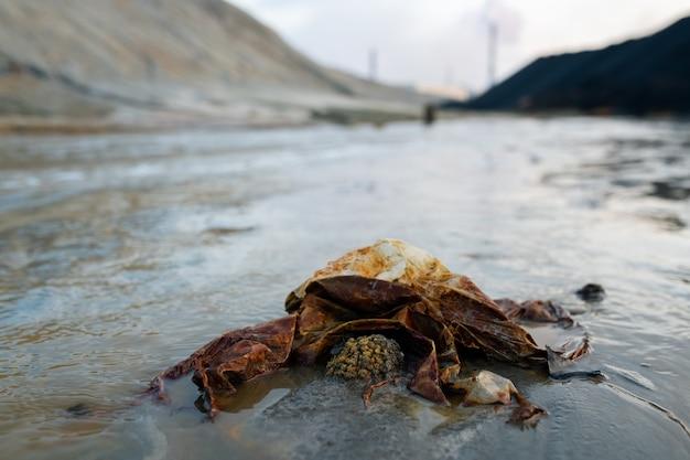 Часть грязной дороги с мусором в большой луже или загрязненной реки в окружении холмов и промышленных предприятий, выбрасывающих токсичные пары в опасную зону